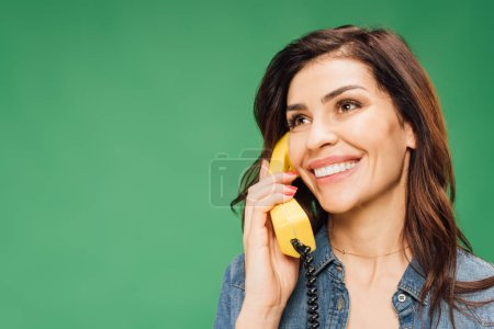 smiling beautiful woman talking on vintage telephone isolated on green