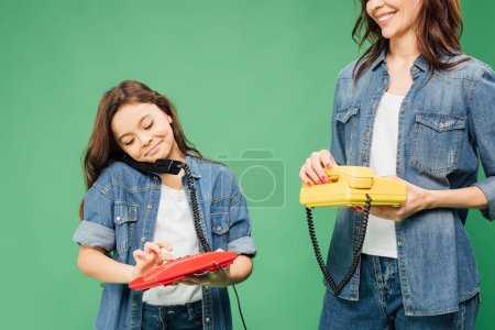 Photo for Mother and smiling daughter holding vintage telephones isolated on green - Royalty Free Image