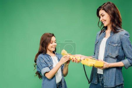 Photo pour Belle mère et la fille tenant le téléphone vintage isolé sur vert - image libre de droit
