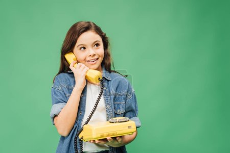 cute smiling child talking on vintage telephone isolated on green