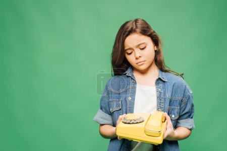 Photo for Sad child in denim holding vintage telephone isolated on green - Royalty Free Image