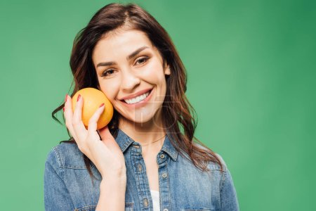 Photo for Smiling woman in denim holding orange and looking at camera isolated on green - Royalty Free Image