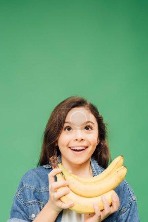 Foto de Emocionado el niño adorable con plátanos aislados en verde - Imagen libre de derechos