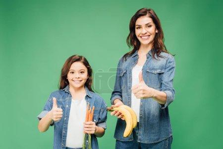 Foto de Madre e hija mostrando los pulgares para arriba y sostiene plátanos con zanahorias aisladas en verde - Imagen libre de derechos