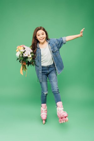 excited child in rollerblades with flower bouquet on green background