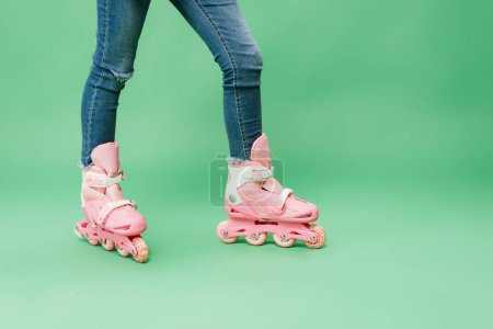 Photo pour Vue partielle de l'enfant portant du denim et des rollers roses isolés sur du vert - image libre de droit