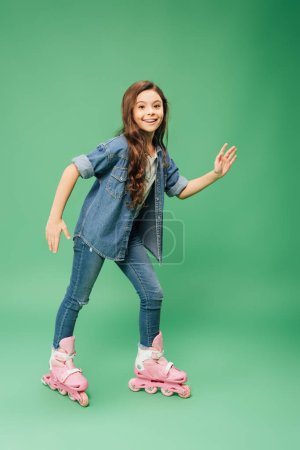 Photo for Smiling child rollerblading with outstretched hands on green background - Royalty Free Image