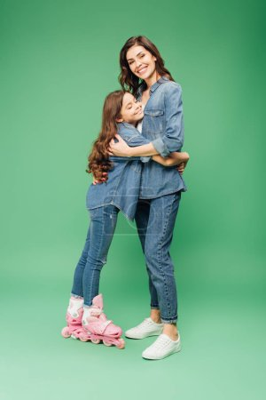 Photo for Daughter in roller blades hugging mother on green background - Royalty Free Image