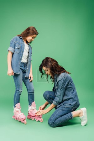 mother in denim putting roller blades on daughter on green background