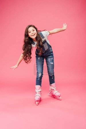 cute smiling child in overalls rollerblading with outstretched hands isolated on pink background