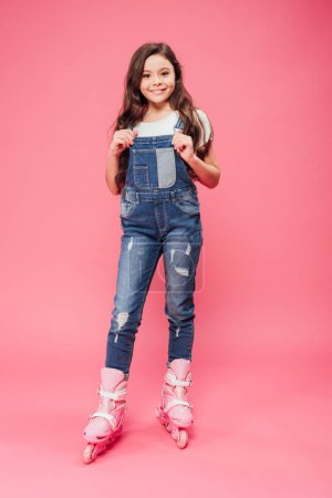 smiling child in overalls and rollerblades looking at camera on pink background