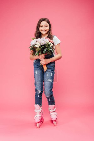 adorable smiling child in rollerblades with flower bouquet on pink background