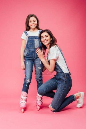 Foto de Madre feliz abrazando a hija en patines y mirando a cámara en fondo rosa - Imagen libre de derechos