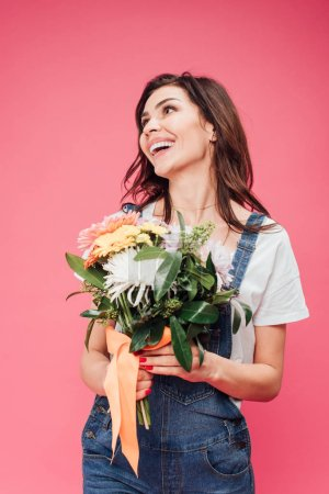 cheerful woman holding flower bouquet isolated on pink