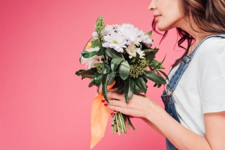 cropped view of woman holding flower bouquet isolated on pink