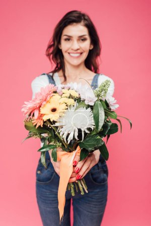 Photo for Smiling woman holding flower bouquet isolated on pink - Royalty Free Image