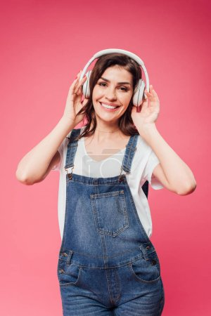 smiling woman listening music in headphones isolated on pink