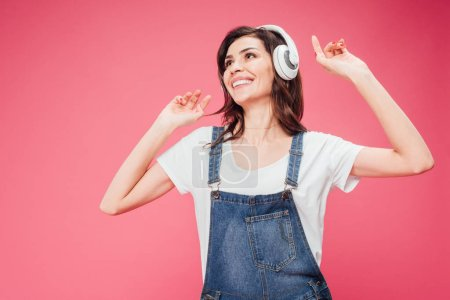 happy woman listening music in headphones isolated on pink
