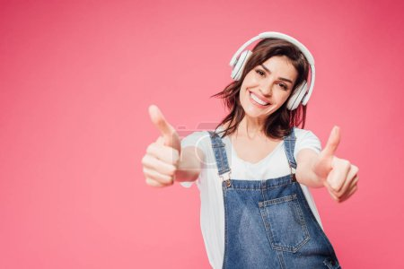 woman listening music in headphones and showing thumbs up isolated on pink
