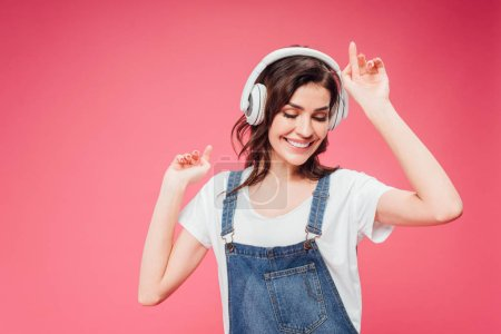Photo pour Femme écouter de la musique dans les écouteurs isolés sur rose - image libre de droit