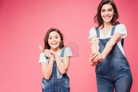 happy mother and daughter holding lollipops and looking at camera isolated on pink