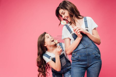cheerful mother and daughter holding lollipops isolated on pink