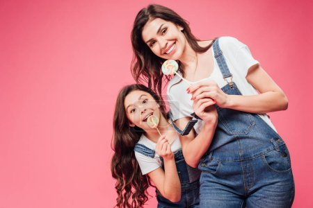 smiling mother and daughter holding lollipops isolated on pink
