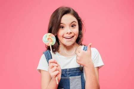 Photo for Smiling child holding lollipop and showing thumb up isolated on pink - Royalty Free Image