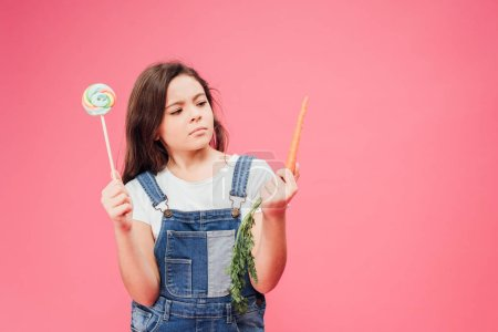 serious child choosing between carrot and candy isolated on pink