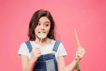 cheerful kid eating lollipop and looking at carrot isolated on pink