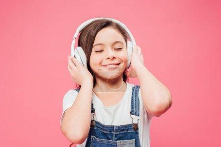 Photo pour Musique enfant souriant dans les écouteurs isolé sur Rose - image libre de droit