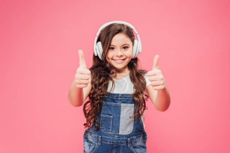 Lächelndes Kind mit Kopfhörern, das vereinzelt Daumen hoch auf rosa zeigt
