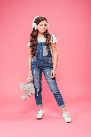 Photo for Full length of sad kid standing in headphones and holding teddy bear on pink background - Royalty Free Image