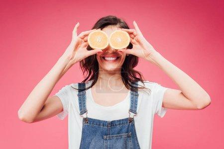 uśmiechnięta kobieta trzymając pomarańcze na oczy na różowym tle