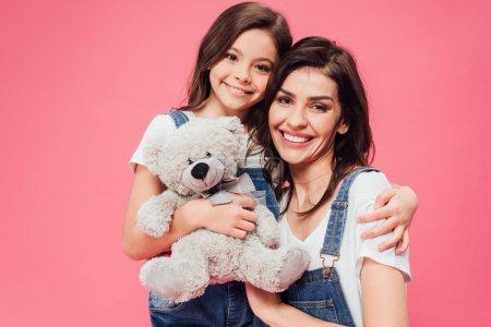 Photo pour Fille souriante étreignant mère et tenant jouet doux isolé sur rose - image libre de droit