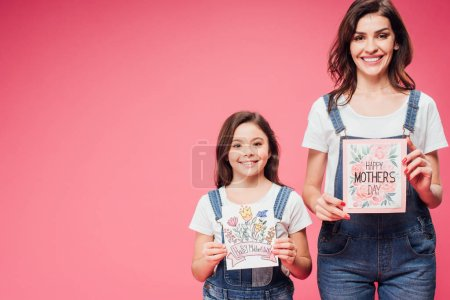 Photo for Mother and daughter holding greeting cards on mothers day isolated on pink - Royalty Free Image