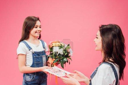 fröhliche Tochter schenkt Mutter am Muttertag Karte und Blumen