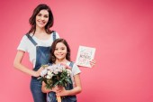 happy mother and daughter smiling while holding flowers and greeting card on mothers day isolated on pink
