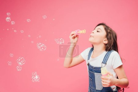 joyful kid blowing soap bubbles isolated isolated on pink
