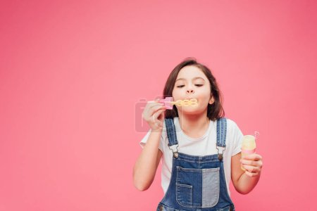 funny kid blowing soap bubbles isolated on pink