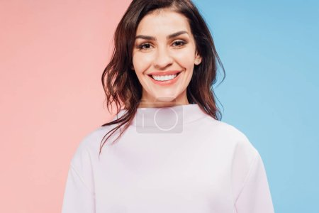Photo for Beautiful woman looking at camera and smiling on blue and pink background - Royalty Free Image