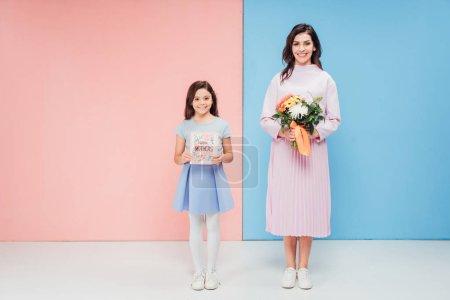 Photo pour Adorable enfant et jolie femme tenant des cadeaux tout en regardant la caméra sur fond bleu et rose - image libre de droit