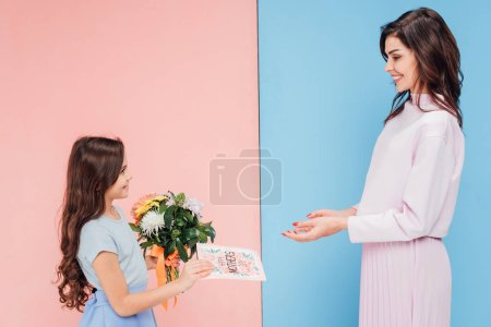 adorable child giving bouquet and greeting card to attractive woman on blue and pink background