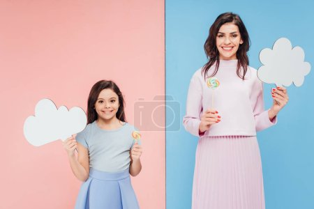 adorable child and attractive woman holding speech bubbles and candies on blue and pink background