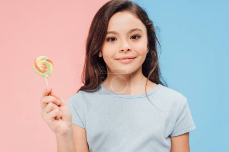 Photo for Adorable child holding candy while looking at camera on blue and pink background - Royalty Free Image