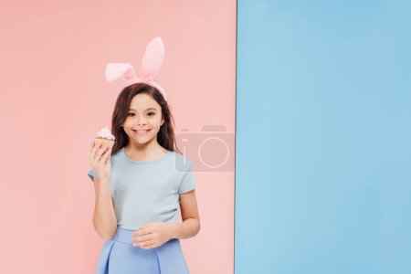 adorable kid in easter bunny ears holding cupcake and looking at camera on blue and pink background