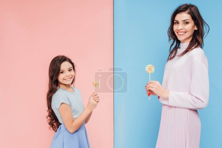 beautiful woman and child holding candies while looking at camera on blue and pink background