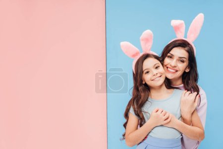 Photo for Beautiful woman in bunny ears hugging child and smiling at camera on blue and pink background - Royalty Free Image