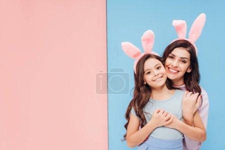 Photo pour Belle femme dans les oreilles de lapin étreignant l'enfant et souriant à la caméra sur fond bleu et rose - image libre de droit