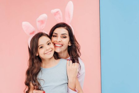 Photo for Beautiful woman in easter bunny ears hugging child and looking at camera on blue and pink background - Royalty Free Image